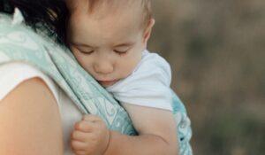 Kleines Kind schläft in mintgrüner Babytrage an der Brust seiner Mutter.