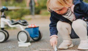 Kleines Mädchen mit Vierrad neben sich malt mit Kreide auf Asphalt.